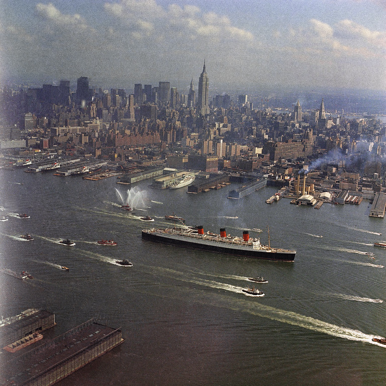 Queen Mary leaves New York for the final time, escorted by small craft