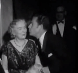 Actor Kenneth More, who played Second Officer Charles Lightoller in the film, pecks the check of the real Mrs. Lightoller.