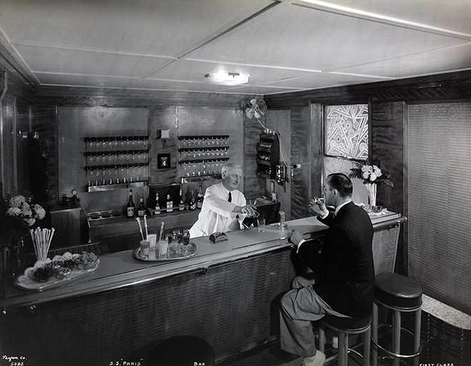 First Class Bar with Chief Barman Georges Che'neau and Cashier Gabriel Maillar posing as a thirsty passenger.